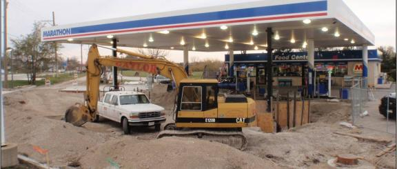 Truck and backhoe at a gas station.